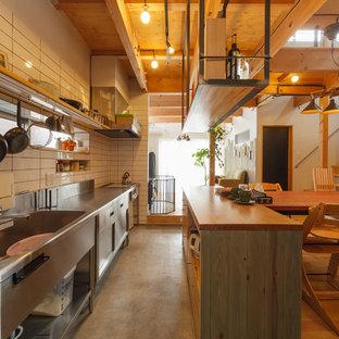 他の地域のインダストリアルスタイルのおしゃれなI型キッチン (シングルシンク、フラットパネル扉のキャビネット、ステンレスキャビネット、ステンレスカウンター、白いキッチンパネル) の写真