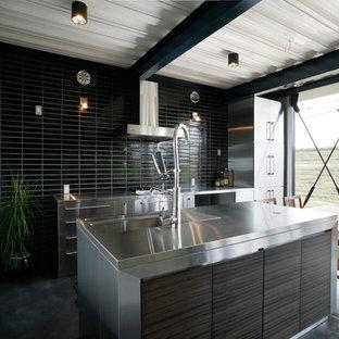 他の地域のミッドセンチュリースタイルのおしゃれなアイランドキッチン (シングルシンク、フラットパネル扉のキャビネット、濃色木目調キャビネット、ステンレスカウンター、黒いキッチンパネル、セラミックタイルのキッチンパネル、シルバーの調理設備、グレーの床) の写真