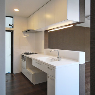 Modern single-wall open plan kitchen in Tokyo with an integrated sink, flat-panel cabinets, white cabinets, composite countertops, white splashback, plywood flooring and brown floors.