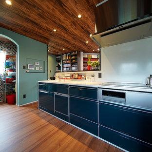 他の地域のインダストリアルスタイルのおしゃれなペニンシュラキッチン (一体型シンク、フラットパネル扉のキャビネット、青いキャビネット、無垢フローリング、茶色い床) の写真