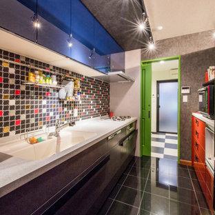 京都の中サイズのコンテンポラリースタイルのおしゃれなキッチン (磁器タイルの床、黒い床、フラットパネル扉のキャビネット、黒いキャビネット、マルチカラーのキッチンパネル、パネルと同色の調理設備、アイランドなし、ベージュのキッチンカウンター) の写真