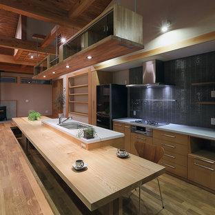 Aménagement d'une cuisine parallèle asiatique avec un évier encastré, un placard à porte plane, des portes de placard en bois clair, une crédence grise, un électroménager en acier inoxydable, un sol en bois brun et un îlot central.