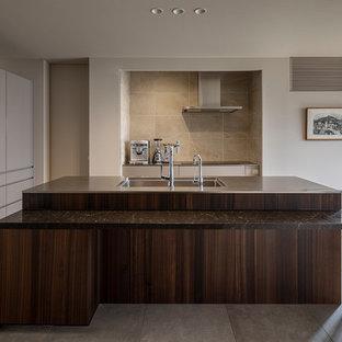 東京23区のモダンスタイルのおしゃれなキッチン (アンダーカウンターシンク、インセット扉のキャビネット、濃色木目調キャビネット、ステンレスカウンター、ベージュキッチンパネル、シルバーの調理設備の、セラミックタイルの床、ベージュの床) の写真