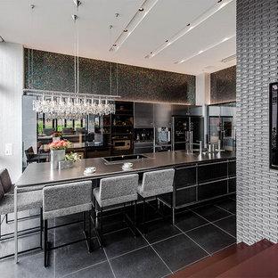 エクレクティックスタイルのおしゃれなキッチン (黒いキャビネット、ステンレスカウンター、黒いキッチンパネル、グレーの床、グレーのキッチンカウンター) の写真