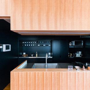 東京23区のコンテンポラリースタイルのおしゃれなキッチン (一体型シンク、インセット扉のキャビネット、青いキャビネット、ステンレスカウンター、茶色いキッチンパネル、木材のキッチンパネル、パネルと同色の調理設備、無垢フローリング、アイランドなし、茶色い床) の写真