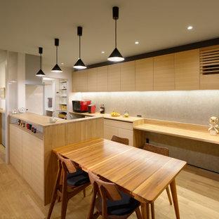 Idée de décoration pour une cuisine américaine parallèle asiatique de taille moyenne avec un placard à porte plane, des portes de placard en bois clair, un plan de travail en bois, une crédence grise, un électroménager encastrable, un sol en bois clair, aucun îlot, un sol beige et un plan de travail beige.