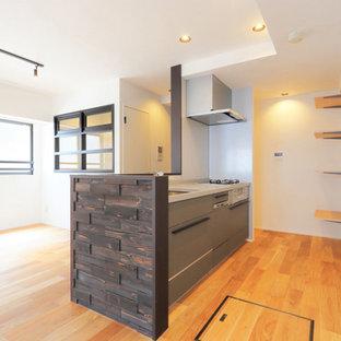 Immagine di una cucina moderna con ante grigie, paraspruzzi grigio, pavimento in legno massello medio, isola, pavimento beige, top marrone e soffitto in carta da parati