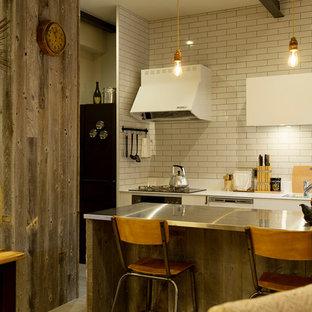 他の地域のインダストリアルスタイルのおしゃれなキッチン (アンダーカウンターシンク、ステンレスカウンター、白いキッチンパネル、サブウェイタイルのキッチンパネル、白い調理設備) の写真