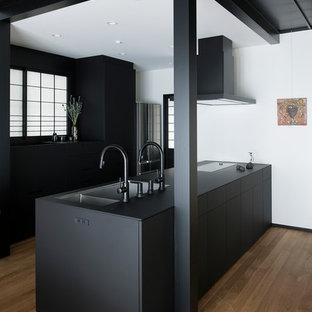 Idéer för att renovera ett orientaliskt svart linjärt svart kök med öppen planlösning, med en undermonterad diskho, luckor med profilerade fronter, svarta skåp, svarta vitvaror, mellanmörkt trägolv, en halv köksö och brunt golv