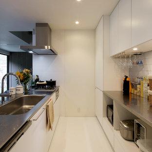 他の地域のモダンスタイルのおしゃれなキッチン (シングルシンク、フラットパネル扉のキャビネット、白いキャビネット、ステンレスカウンター、白いキッチンパネル、白い床) の写真
