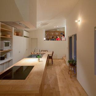 Modelo de cocina de galera, moderna, de tamaño medio, cerrada, con fregadero integrado, armarios estilo shaker, puertas de armario de madera clara, encimera de madera, salpicadero blanco, electrodomésticos blancos, suelo de madera clara, una isla, suelo beige y encimeras beige