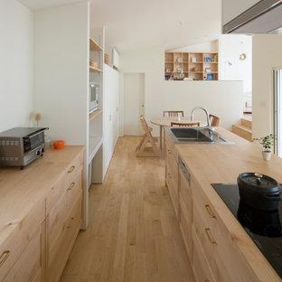 名古屋の中くらいのアジアンスタイルのおしゃれなキッチン (ドロップインシンク、淡色木目調キャビネット、木材カウンター、シルバーの調理設備、淡色無垢フローリング、茶色い床、ベージュのキッチンカウンター、シェーカースタイル扉のキャビネット、白いキッチンパネル、塗装板のキッチンパネル) の写真