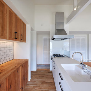 Inspiration for a contemporary galley open plan kitchen in Other with medium wood cabinets, an integrated sink, flat-panel cabinets, stainless steel appliances and medium hardwood floors.
