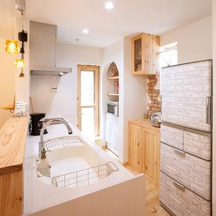 他の地域のアジアンスタイルのおしゃれなキッチン (一体型シンク、中間色木目調キャビネット、白いキッチンパネル、淡色無垢フローリング、茶色い床) の写真