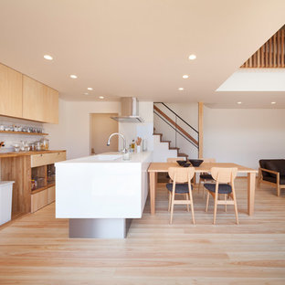Inspiration for a scandinavian open plan kitchen in Other with an integrated sink, flat-panel cabinets, light wood cabinets, wood benchtops, white splashback, subway tile splashback, light hardwood floors, with island, beige floor and beige benchtop.