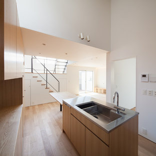 Modern single-wall kitchen/diner in Tokyo with a submerged sink, flat-panel cabinets, medium wood cabinets, stainless steel worktops, brown splashback, wood splashback, stainless steel appliances, plywood flooring, an island and brown floors.