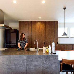 他の地域のアジアンスタイルのおしゃれなキッチン (シングルシンク、フラットパネル扉のキャビネット、濃色木目調キャビネット、黒い調理設備、グレーのキッチンカウンター) の写真
