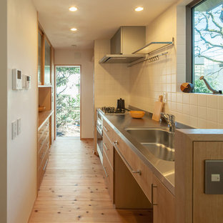 This is an example of a small modern single-wall open plan kitchen in Tokyo with an integrated sink, flat-panel cabinets, light wood cabinets, stainless steel benchtops, white splashback, stainless steel appliances, light hardwood floors, porcelain splashback, with island and brown floor.