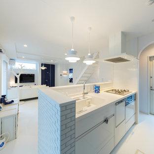 東京都下の中くらいの北欧スタイルのおしゃれなキッチン (一体型シンク、フラットパネル扉のキャビネット、白いキャビネット、人工大理石カウンター、メタリックのキッチンパネル、セラミックタイルのキッチンパネル、白い調理設備、白い床、白いキッチンカウンター) の写真