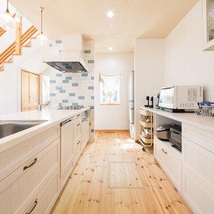 他の地域のカントリー風おしゃれなキッチン (白いキッチンパネル、淡色無垢フローリング、マルチカラーの床、白いキッチンカウンター) の写真