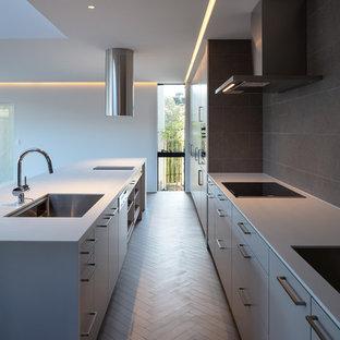 Свежая идея для дизайна: параллельная кухня в стиле модернизм с одинарной раковиной, плоскими фасадами, серыми фасадами, деревянным полом, островом, серым полом и белой столешницей - отличное фото интерьера
