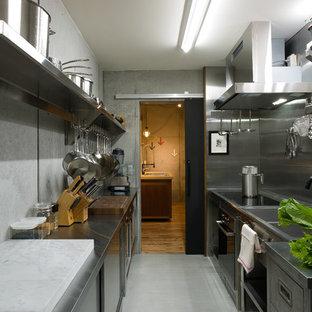他の地域のインダストリアルスタイルのおしゃれなキッチン (ダブルシンク、フラットパネル扉のキャビネット、ステンレスキャビネット、ステンレスカウンター、メタリックのキッチンパネル、コンクリートの床、アイランドなし、グレーの床) の写真