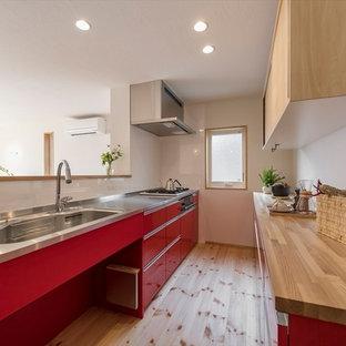 横浜の北欧スタイルのおしゃれなペニンシュラキッチン (シングルシンク、フラットパネル扉のキャビネット、赤いキャビネット、ステンレスカウンター、無垢フローリング、茶色い床、茶色いキッチンカウンター) の写真