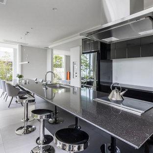 コンテンポラリースタイルのおしゃれなキッチン (黒いキャビネット、黒いキッチンパネル、黒い調理設備、ベージュの床、シングルシンク、フラットパネル扉のキャビネット) の写真