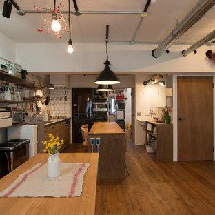 東京都下のおしゃれなキッチン (シングルシンク、フラットパネル扉のキャビネット、中間色木目調キャビネット、ステンレスカウンター、白いキッチンパネル、無垢フローリング、茶色い床、茶色いキッチンカウンター) の写真