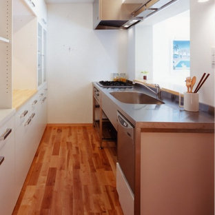 Design ideas for a small contemporary single-wall open plan kitchen in Tokyo with an integrated sink, open cabinets, stainless steel cabinets, stainless steel benchtops, white splashback, slate splashback, stainless steel appliances, medium hardwood floors, a peninsula and brown floor.