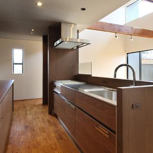 他の地域の広いアジアンスタイルのおしゃれなキッチン (一体型シンク、フラットパネル扉のキャビネット、茶色いキャビネット、ステンレスカウンター、茶色いキッチンパネル、木材のキッチンパネル、シルバーの調理設備、無垢フローリング、茶色い床、茶色いキッチンカウンター) の写真