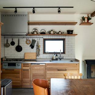 他の地域のアジアンスタイルのおしゃれなキッチン (シェーカースタイル扉のキャビネット、中間色木目調キャビネット、白いキッチンパネル、コンクリートの床、グレーの床、グレーのキッチンカウンター) の写真