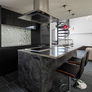 東京23区の広いI型モダンスタイルのLDKの画像 (黒いキャビネット、ステンレスカウンター、黒いキッチンパネル、アイランド1つ、黒い床)