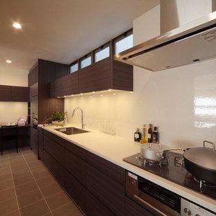 東京23区のモダンスタイルのおしゃれなキッチン (シングルシンク、フラットパネル扉のキャビネット、中間色木目調キャビネット、白いキッチンパネル、グレーの床) の写真