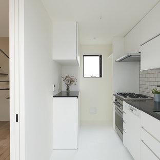 東京23区の小さいモダンスタイルのおしゃれなキッチン (アンダーカウンターシンク、インセット扉のキャビネット、白いキャビネット、人工大理石カウンター、白いキッチンパネル、木材のキッチンパネル、白い調理設備、クッションフロア、白い床、黒いキッチンカウンター) の写真