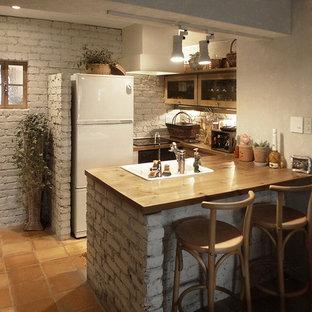 東京23区の小さいカントリー風おしゃれなキッチン (シングルシンク、木材カウンター、テラコッタタイルの床、オレンジの床、茶色いキッチンカウンター) の写真