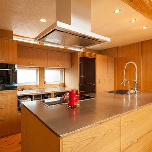 他の地域のモダンスタイルのおしゃれなキッチン (シングルシンク、フラットパネル扉のキャビネット、中間色木目調キャビネット、ステンレスカウンター、無垢フローリング、茶色い床) の写真