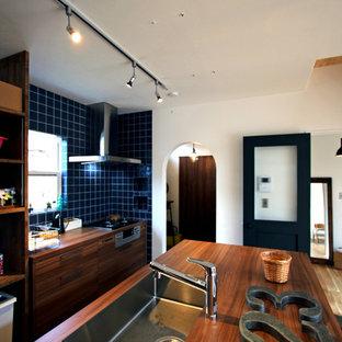 他の地域のモダンスタイルのおしゃれなキッチン (一体型シンク、インセット扉のキャビネット、濃色木目調キャビネット、ラミネートカウンター、青いキッチンパネル、磁器タイルのキッチンパネル、黒い調理設備、無垢フローリング、茶色い床) の写真