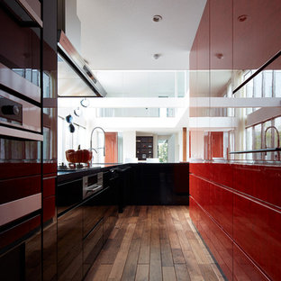 Foto de cocina actual, de tamaño medio, con armarios con paneles lisos, electrodomésticos de acero inoxidable y península