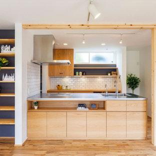 Imagen de cocina lineal, contemporánea, con fregadero de un seno, armarios con paneles lisos, encimera de acero inoxidable, salpicadero blanco, salpicadero de azulejos de piedra, suelo de madera clara, una isla y puertas de armario de madera clara