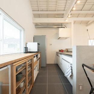 他の地域のアジアンスタイルのおしゃれなキッチン (フラットパネル扉のキャビネット、白いキャビネット、ステンレスカウンター、グレーの床) の写真