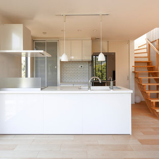 他の地域のモダンスタイルのおしゃれなキッチン (一体型シンク、フラットパネル扉のキャビネット、白いキャビネット、黒い調理設備、淡色無垢フローリング、ベージュの床、白いキッチンカウンター) の写真