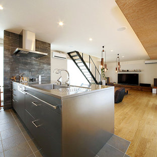 Photo of a large modern galley open plan kitchen in Other with flat-panel cabinets, a peninsula, an integrated sink, medium wood cabinets, stainless steel benchtops, grey splashback, stone tile splashback, stainless steel appliances and ceramic floors.