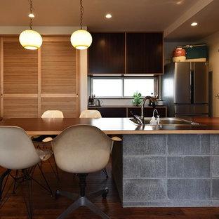 他の地域のアジアンスタイルのおしゃれなペニンシュラキッチン (シングルシンク、濃色無垢フローリング、茶色い床) の写真