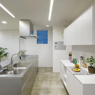 他の地域のモダンスタイルのおしゃれなキッチン (シングルシンク、フラットパネル扉のキャビネット、ステンレスキャビネット、ステンレスカウンター、コンクリートの床、グレーの床) の写真