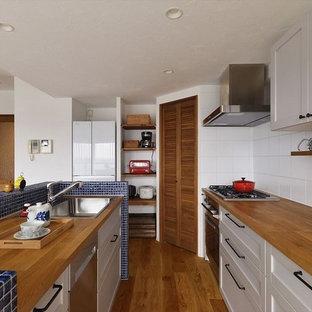 地中海スタイルのおしゃれなキッチン (シングルシンク、落し込みパネル扉のキャビネット、白いキャビネット、木材カウンター、青いキッチンパネル、セラミックタイルのキッチンパネル、無垢フローリング、茶色い床、茶色いキッチンカウンター) の写真