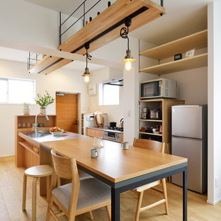 Bild på ett orientaliskt grå grått kök, med en integrerad diskho, släta luckor, skåp i mellenmörkt trä, bänkskiva i rostfritt stål, rostfria vitvaror, ljust trägolv, en köksö och beiget golv