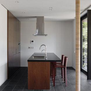 他の地域のトラディショナルスタイルのおしゃれなキッチン (アンダーカウンターシンク、インセット扉のキャビネット、濃色木目調キャビネット、クオーツストーンカウンター、黒い調理設備、セラミックタイルの床、グレーの床、黒いキッチンカウンター) の写真