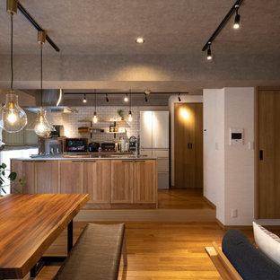 他の地域の中サイズのインダストリアルスタイルのおしゃれなキッチン (シェーカースタイル扉のキャビネット、ベージュのキャビネット、白いキッチンパネル、サブウェイタイルのキッチンパネル、パネルと同色の調理設備、無垢フローリング、ベージュの床、グレーのキッチンカウンター) の写真