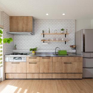 他の地域の中サイズのコンテンポラリースタイルのおしゃれなI型キッチン (一体型シンク、フラットパネル扉のキャビネット、ベージュのキャビネット、ステンレスカウンター、白いキッチンパネル、サブウェイタイルのキッチンパネル、シルバーの調理設備の、アイランドなし、ベージュの床、グレーのキッチンカウンター) の写真